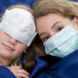 Sisters in bed with protective mask — Stock Photo