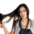 Stock Photo: Woman brushing her hair