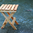 Lonely wooden folding stool - Stock Photo