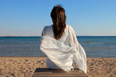 Vrouw zittend op strand — Stockfoto