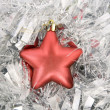Red star, christmas decoration on silver tinsel — Stock Photo