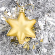 Golden star, christmas decoration on silver tinsel — Stock Photo #4504572