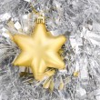 Royalty-Free Stock Photo: Golden star, christmas decoration on silver tinsel