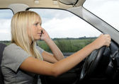 Woman with mobile phone in the car — Stock Photo
