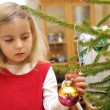 Girl decorating christmas tree - Stock Photo