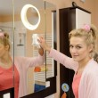 Housewife cleans a mirror — Stock Photo