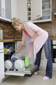 Housewife at the dishwasher — Stock Photo