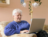 Elderly woman working on laptop — Stockfoto