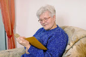 Elderly woman reads a book — Stock Photo