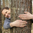 Young woman hugging a tree — Stock Photo