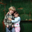 Royalty-Free Stock Photo: Young brother and sister pose for a photograph with their camera