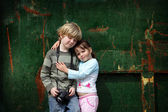 Young brother and sister pose for a photograph with their camera — Stock Photo