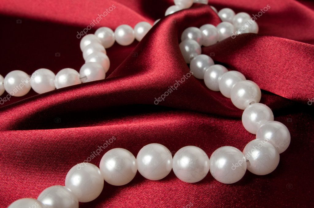 A pearl necklace on red satin — Stock Photo #4233044
