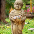 Stony buddhist monk sculpture with bowl — Stock Photo