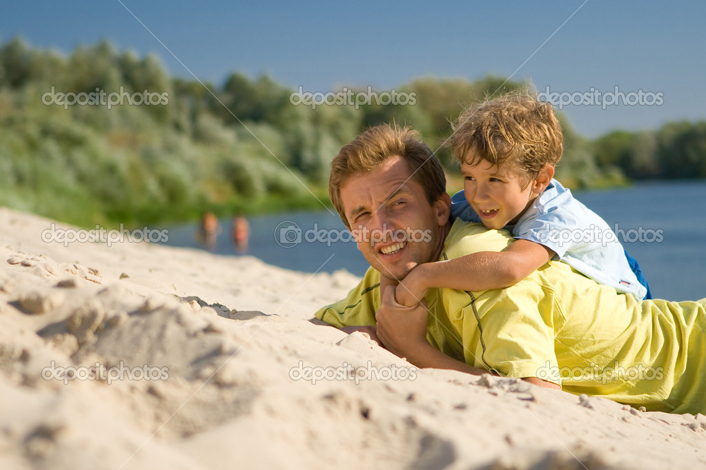 The father and the son lie on sandy to river bank and smile — Stock Photo #3925178