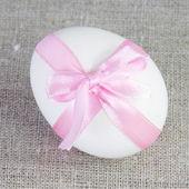 Jediné bílé velikonoční vajíčko s růžovou mašlí — Stock fotografie