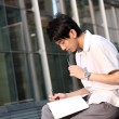 Casual asian businessman texting on his book — Stock Photo