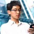 Casual asian businessman texting on his cell phone — Stockfoto