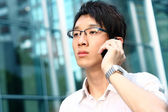 Casual asian businessman talking on his cell phone — Stock Photo