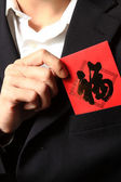 Businessman putting chinese cash gift in his pocket — Stock Photo