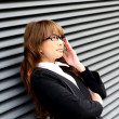 Beautiful young woman posing in business suit and glasses. — Stock Photo