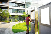 Asia boy play the touch screen in modern building outside — Stock Photo