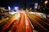 Blurred bus light trails in downtown night-scape — ストック写真