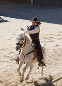 Deputy Sheriff firing his gun on horseback — Stock Photo