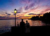 Romantic couple watching the sunset — Stock Photo