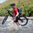 Stock Photo: Biker goes over the mountain river ford
