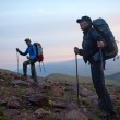 Two tourists at dawn in mountains — Stock Photo