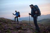 Twee toeristen bij dageraad in bergen — Stockfoto