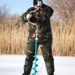 Fisherman drill on winter lake — Stock Photo