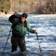 Backpacker wade rugged river — Stock Photo #5027847