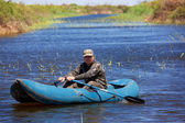 Fisherman in rubber boat on the river — Stock Photo