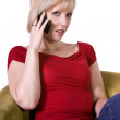 Woman talking on mobile phone at her home — Stock Photo