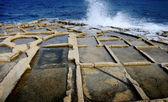 Wave crashing against saltpans — Stock Photo