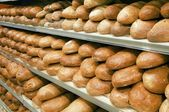 Loaves of bread on shelves — Stock Photo