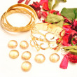 Gold bangles and decorative glass pebbles, dried flowers — Stock Photo