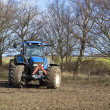 Stock Photo: Blue tractor cultivating