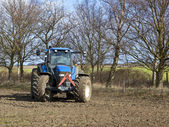 Blue tractor cultivating — Stock Photo