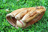 Baseball glove and ball laying in grass — Stock Photo
