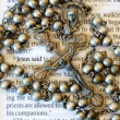 Vintage rosary beads on page of a bible. - Stock Photo