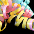 Colorful curling ribbons on black background. - Stock Photo