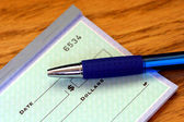 Portion of check with pen — Stock Photo