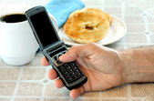 Open cellphone in mans hand at the breakfast table. — Stock Photo