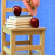 Vintage child's chair stacked with school books. - Stock Photo