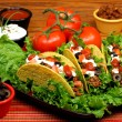 Tacos in a bed of greens with tomatoes and garnishes to the side. - ストック写真