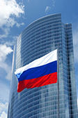 Russian flag on the background of the windows of office building — Stock Photo