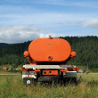 Stock Photo: Green field - Mountain Landscape. Orange machine to irrigate
